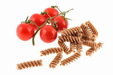 Formati di pasta cruda con pomodorini isolati su sfondo bianco