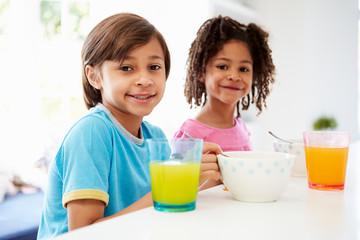 Two Children Having Breakfast In Kitchen Together