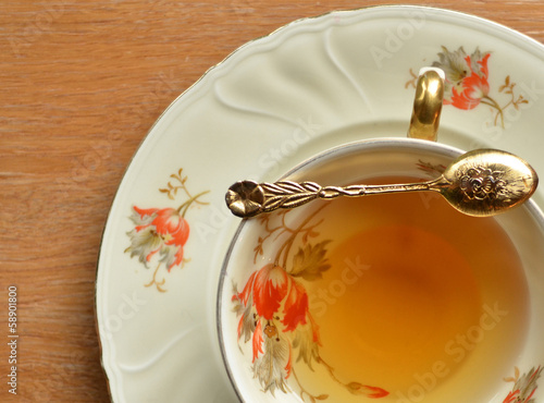 Cup of tea and teaspoon on wooden