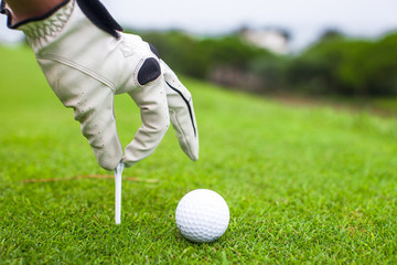 hand placing golf ball on tee over beautiful golf course with