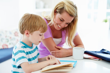 Mother Helping Son With Homework In Kitchen