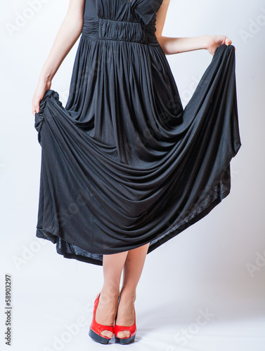 redhead waist down body in black dress,studio shot