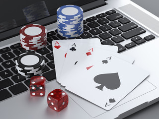laptop with gambling chips and poker cards