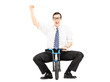 Excited young businessman riding a small bicycle and gesturing
