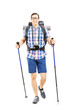 Smiling hiker with backpack and hiking poles walking