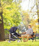 Grandfather on bench with his nephew in a stroller, in a park