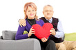 Wife and her husband sitting on a sofa and holding a red heart