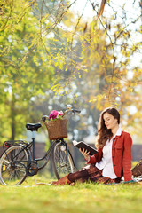 Young beautiful female reading a novel in a park