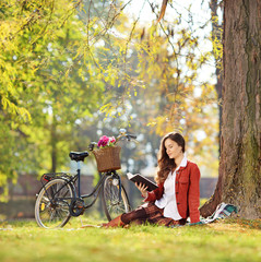 Young beautiful female with her bike, reading a novel in park