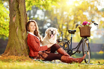 Young female sitting on a grass with her dog in a park