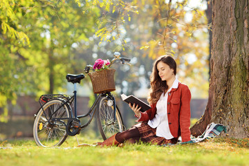 Young woman with a bike reading a novel in a park