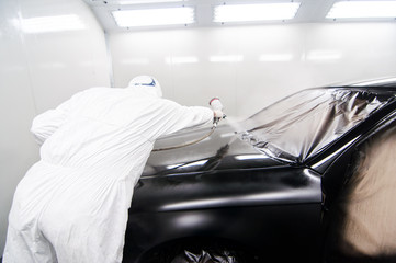 man painting a car in special garage and wearing protective gear