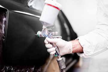 Worker using a paint spray gun for painting a car