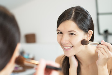 Attractive happy woman applying makeup