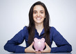 Happy smiling woman holding a piggy bank against gray background