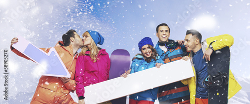 Laughing group of snowboarders with the snowing background