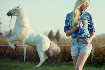Alluring blonde beauty with majestic horse