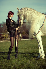 Attractive and shapely redhead with horse