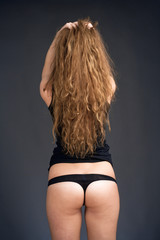 Rear View of a Young Girl with Long Brown Hair in Black Top and