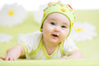 smiling baby lying on green
