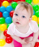 Top view of baby girl playing with colorful balls