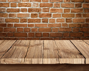 Wooden table and brick background - Stock Image