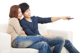 young couple on sofa watching TV with remote control