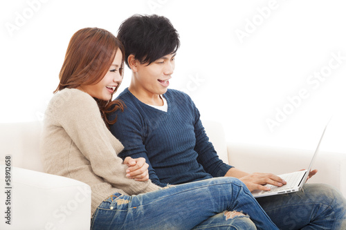 happy Couple in sofa with laptop  at home