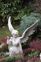 Engel spielt Flöte auf dem Friedhof