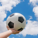 Classic soccer ball on hand with blue sky.