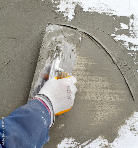 Mason spreading  mortar to styrofoam insulation with trowel