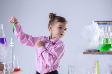 Attentive schoolgirl conducting experiment in lab