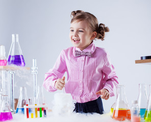 Merry little girl posing with variety of flasks