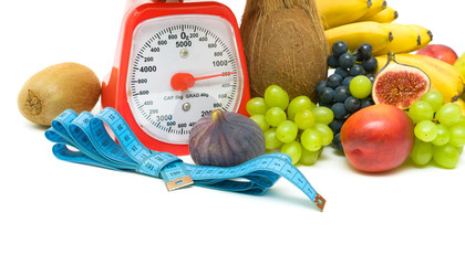 measuring tape, scales and fruits on white background