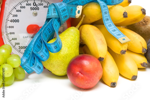 measuring tape, kitchen scales and fresh fruit closeup.