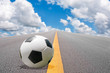 Soccer ball on the road with blue sky