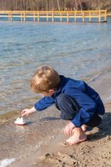 Kleiner Junge spielt am Seeufer mit einem Spielzeugschiff