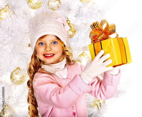 Child in hat and mittens holding Christmas  gift box.