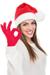 Cute young woman with Santa hat showing ok gesture