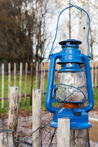 Blue vintage kerosene lamp hangs on wooden outdoor fence