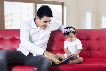 Father and baby reading story book together