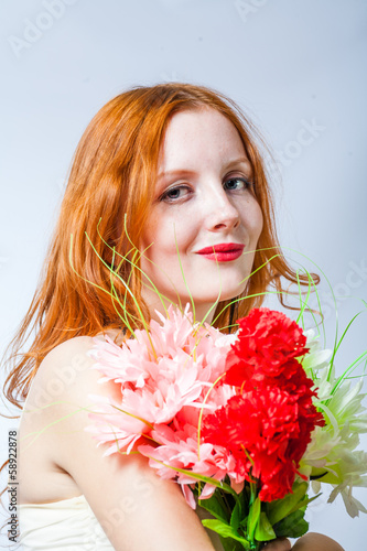 redhead with bunch of flowers in studio on white