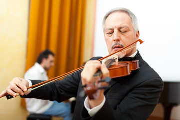 Man playing violin with a pianist