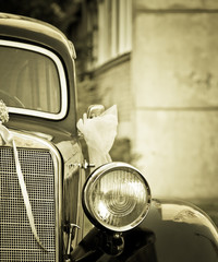 Old timer car with wedding decoration in sepia