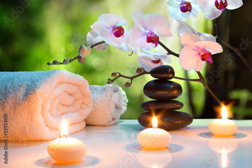 massage composition spa with candles, orchids, stones in garden - 58924618