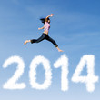 Woman jumping with new year 2014 of clouds