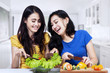 Young women prepare salad together