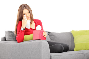 Sad young female on a sofa wiping her eyes from crying
