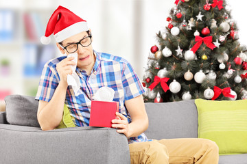 Sad male on a sofa crying with christmas tree in the back