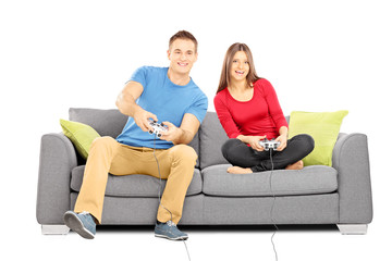 Young couple sitting on a modern couch and playing video games